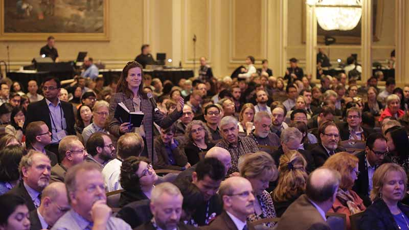 A woman stands at a microphone to ask a question, the rest of the audience sitting around her.