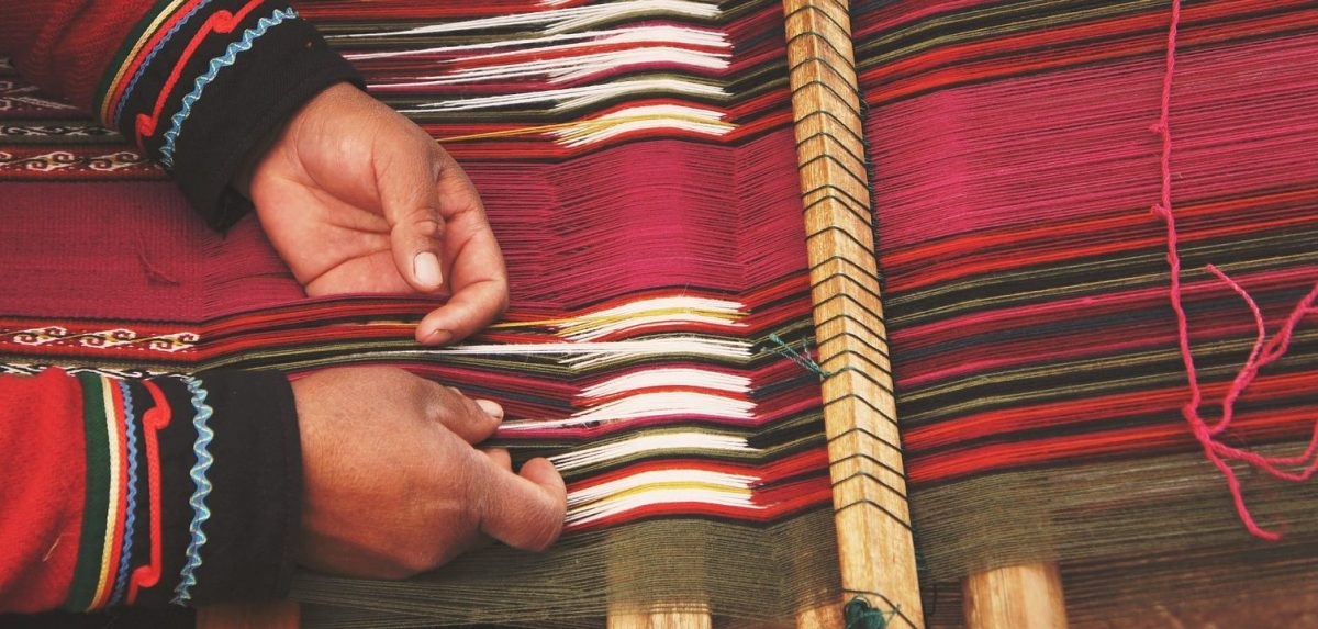 Close-up of hands working threads on a loom