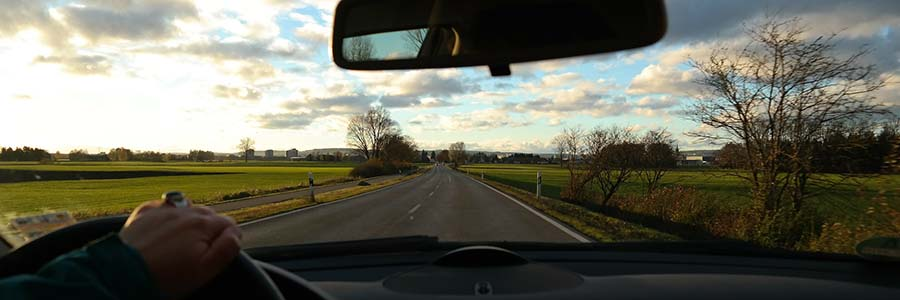 view through a car's windshield of the road and surrounding countryside