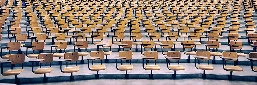 row upon row of empty seats in a large lecture hall