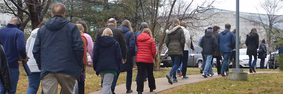a large group of people wearing winter jackets and coats walk down a sidewalk away from the camera